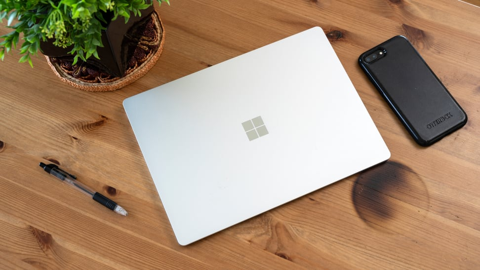 A Microsoft Surface 3 laptop on a brown table. Besides the laptop are a smartphone, a pen, and an indoor plant.