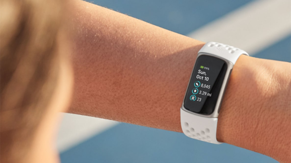A person looking at their Fitbit Charge 5 on their wrist.