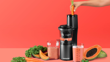 A NutriBullet Slow Juicer is in the center of the image. A person is pushing a carrot through the juicer. There are papayas, carrots, and melon scattered around the juicer.