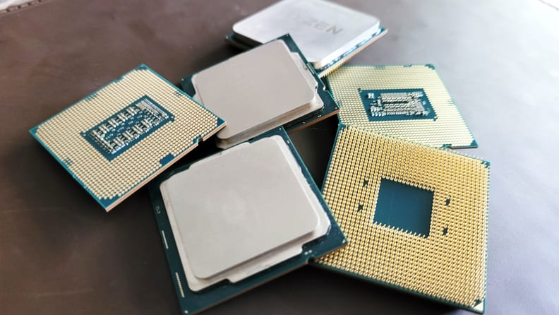 Several desktop computer processors laying a dark surface
