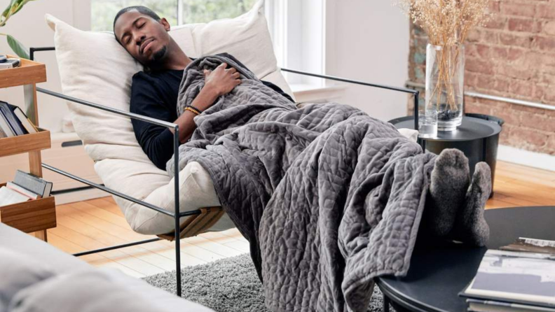A person lays down with a weighted blanket.