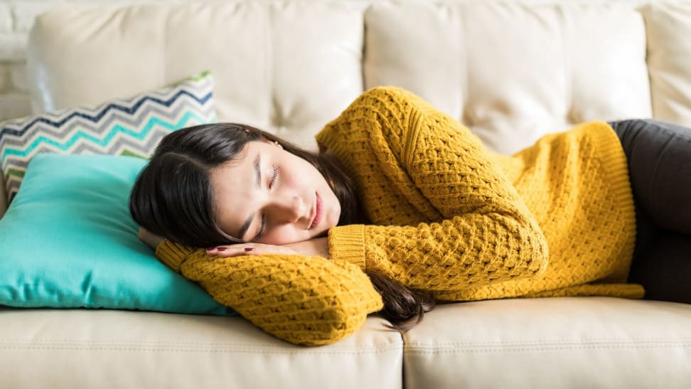 a woman naps in a yellow sweater on her beige couch