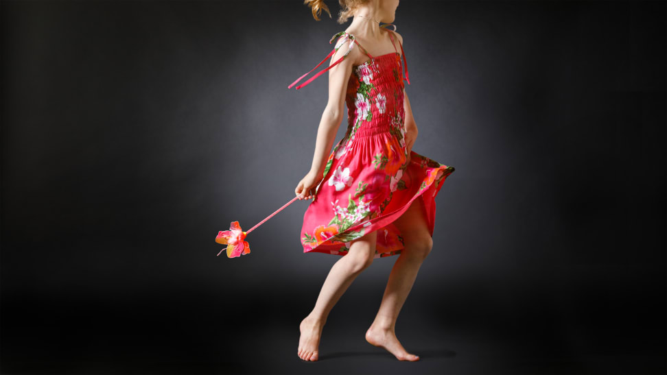 A young girl wearing a pink sundress and dancing with a wand