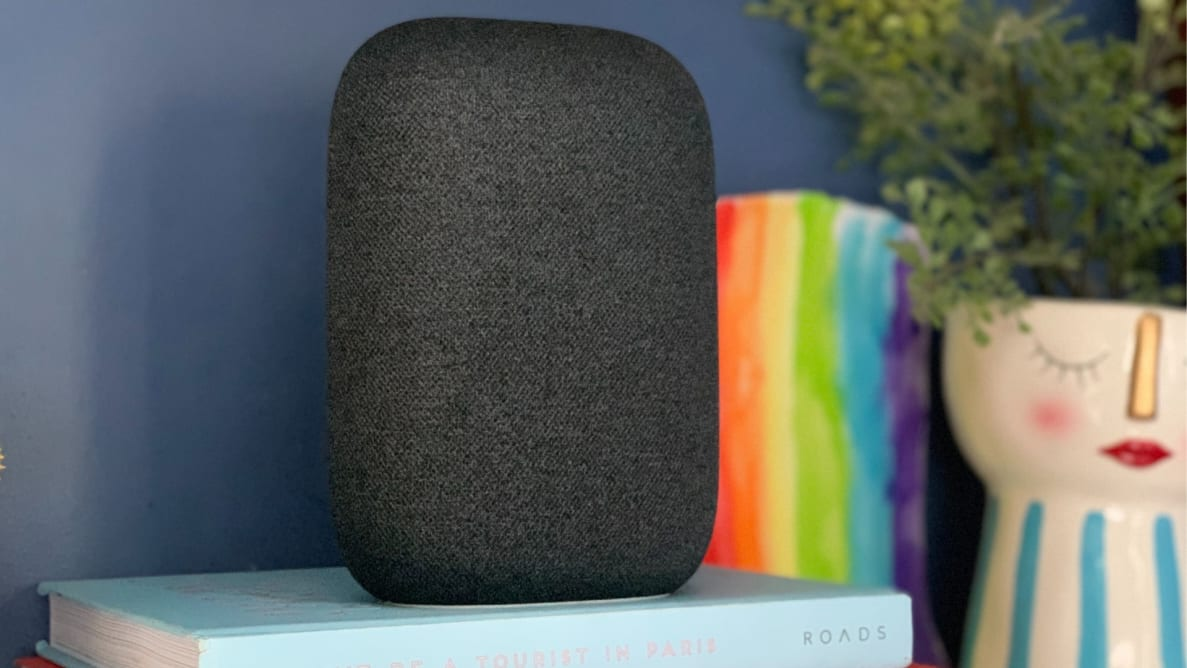 Nest Audio smart speaker sits on atop a pile of books.