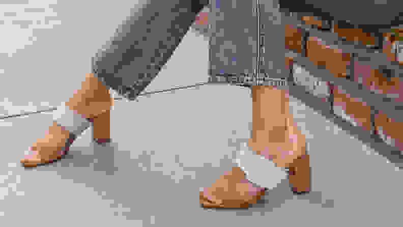 Woman on sidewalk wearing white Chinese Laundry heeled sandals.