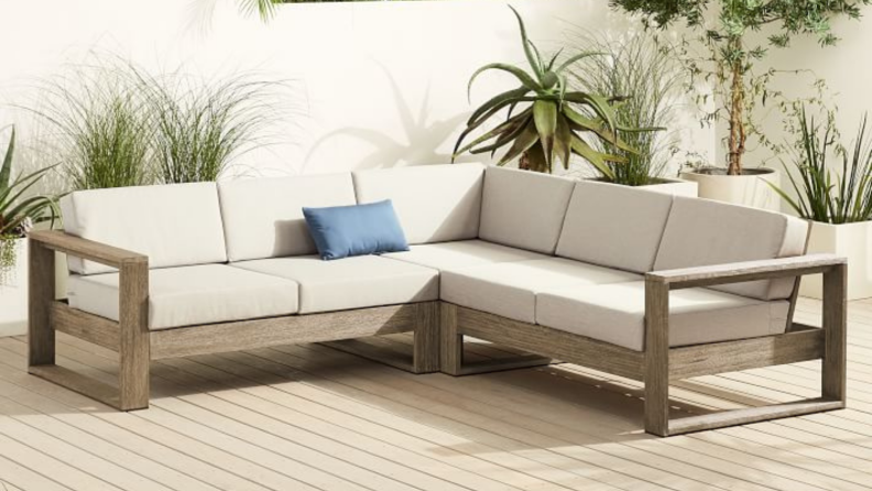 An l-shaped outdoor sofa with white cushions.