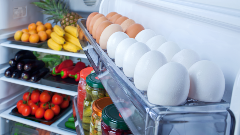 The inside of an open fridge that's fully stocked with eggs, fruits, and vegetables