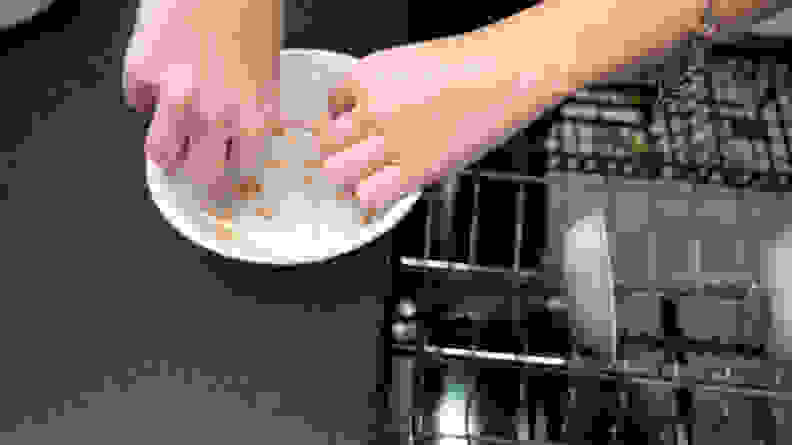 A person measures food stains on a white bowl with a measuring tape