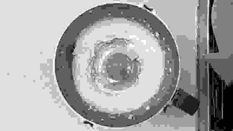 A top-down photo of a food processor filled with whipped feta.