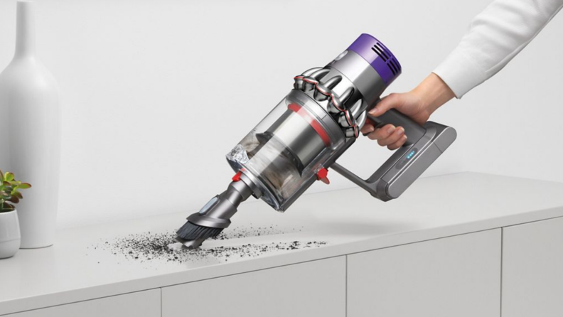 A person vacuums a mess with a Dyson vacuum.