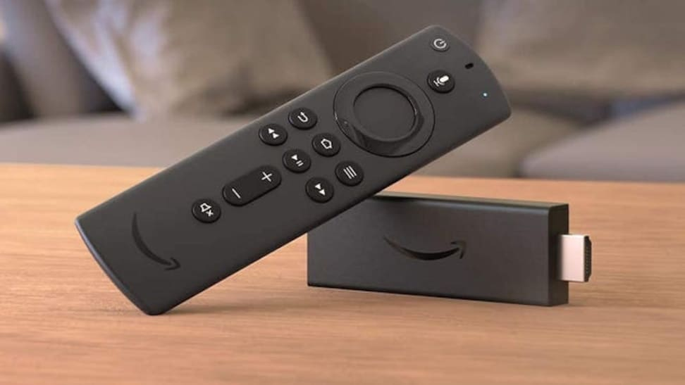 An Amazon Fire Stick, streaming device, leaning against itself on a wooden tabletop.