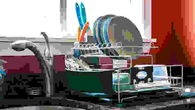 A dish rack full of crockery and cutlery.