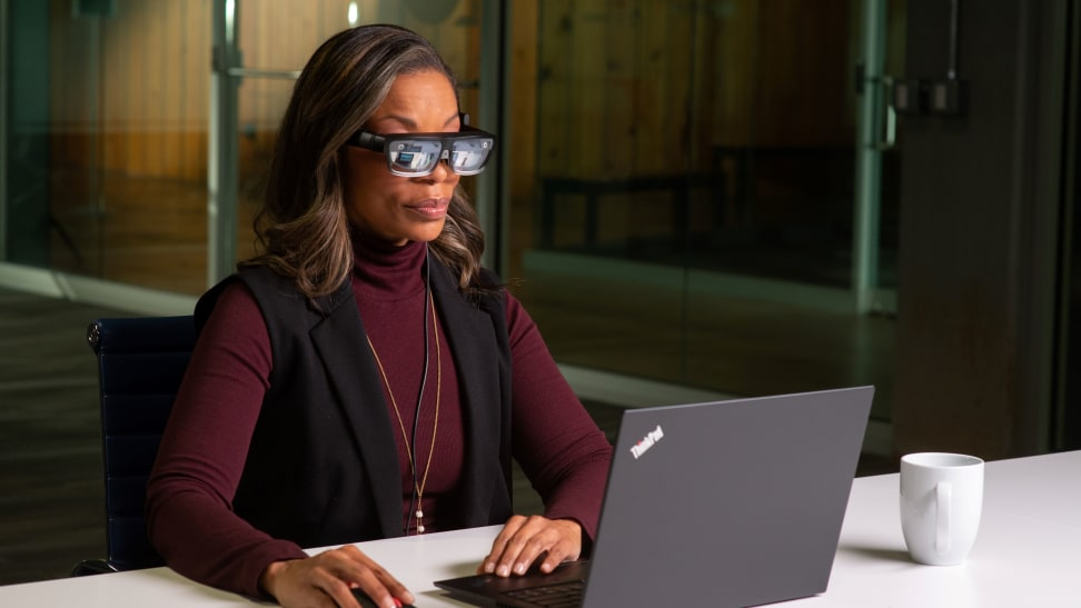 A woman looks at her computer through smart glasses.