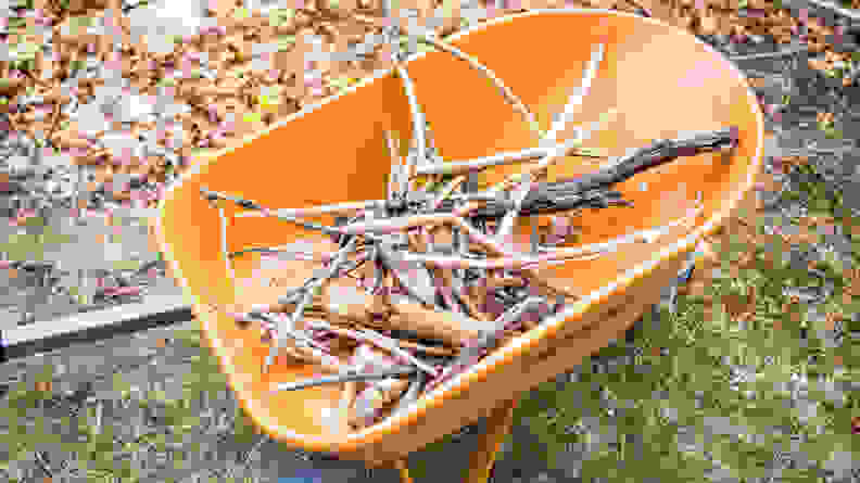 An orange wheelbarrow holds a bundle of branches and sticks.