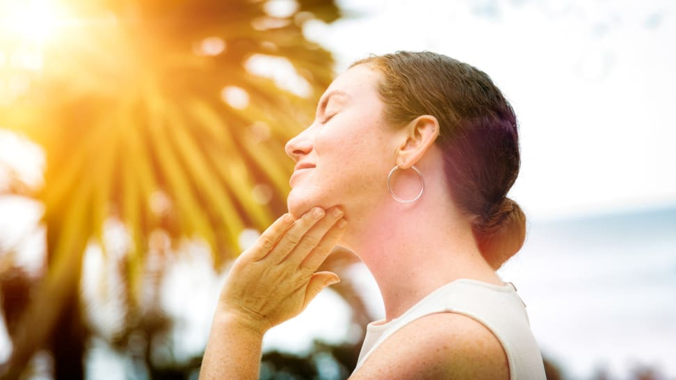 A woman standing in the sun with her hand placed under her chin