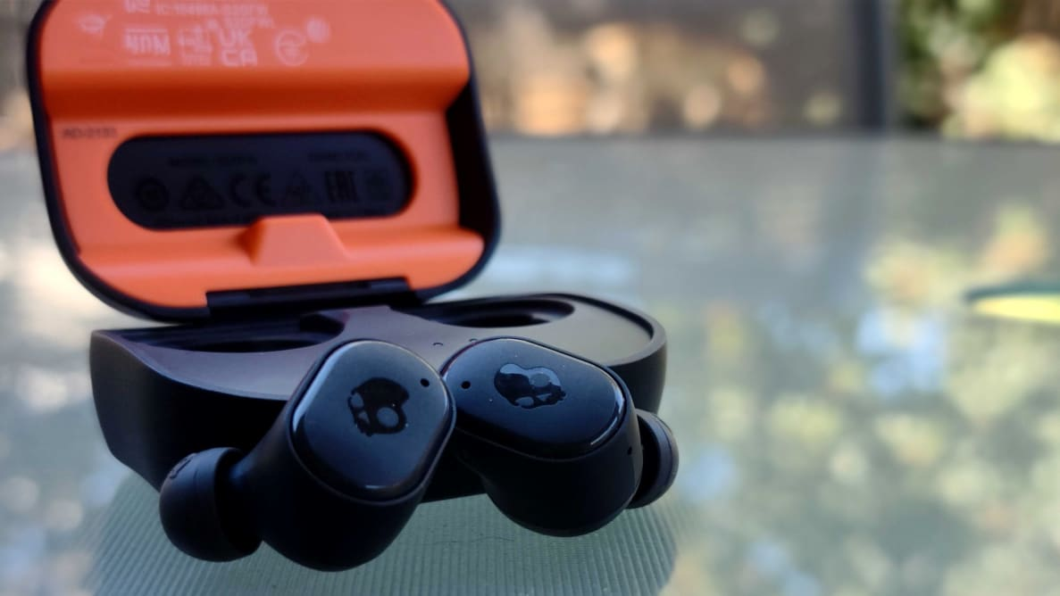 The SkullCandy Grind Fuel earbuds sit in all black with a skull logo along a glass-top table outside, their case open behind showing a bright orange interior.