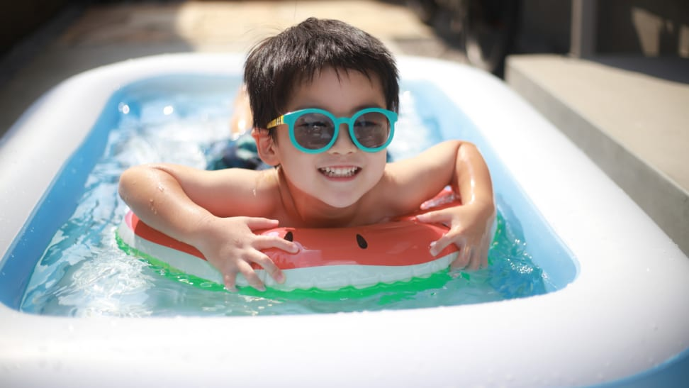 Kid riding a watermelon float in an inflatable pool