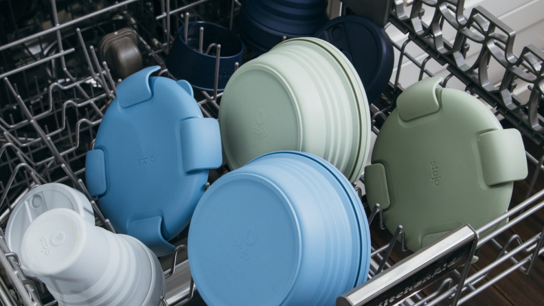 On the top rack of a dishwasher, there are some Stojo products.