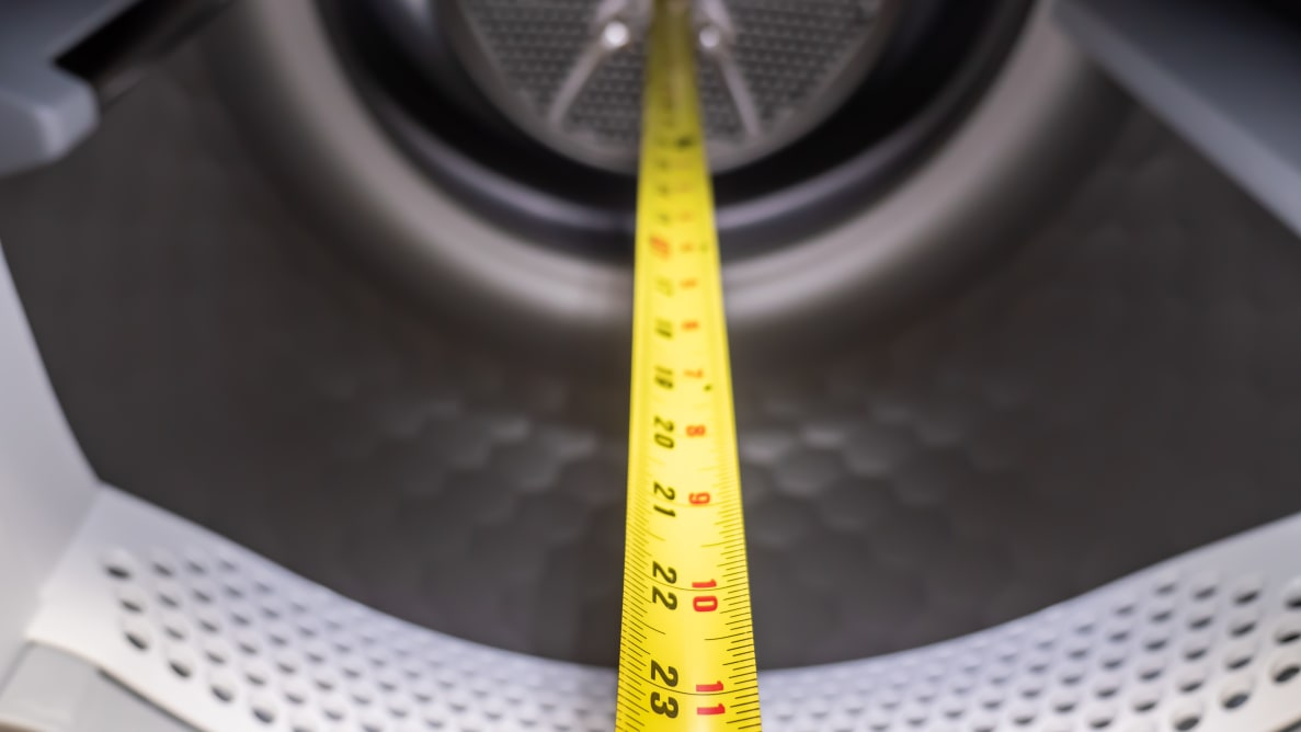 A yellow measuring tape shows that this dryer drum is slightly more than 23 inches
