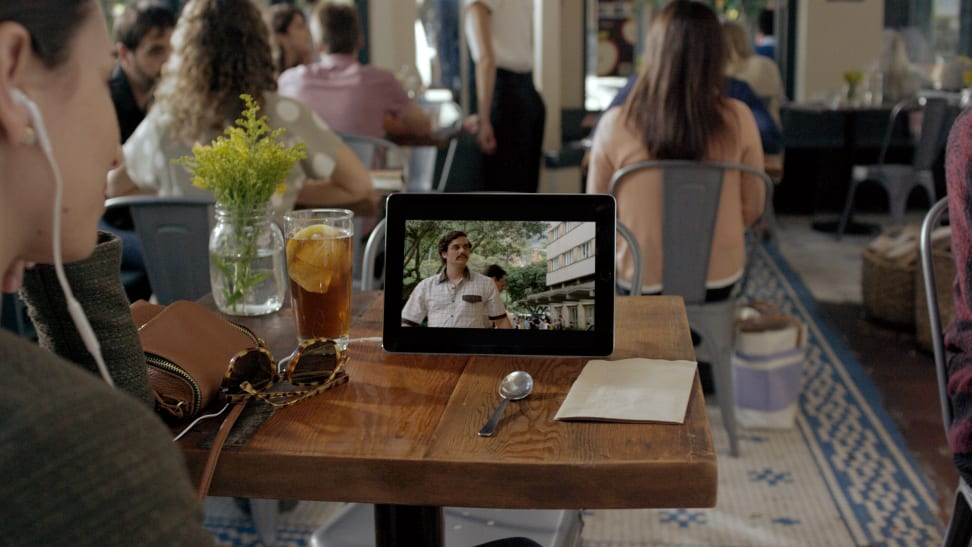 A person watching a Netflix show on their mobile device on a table
