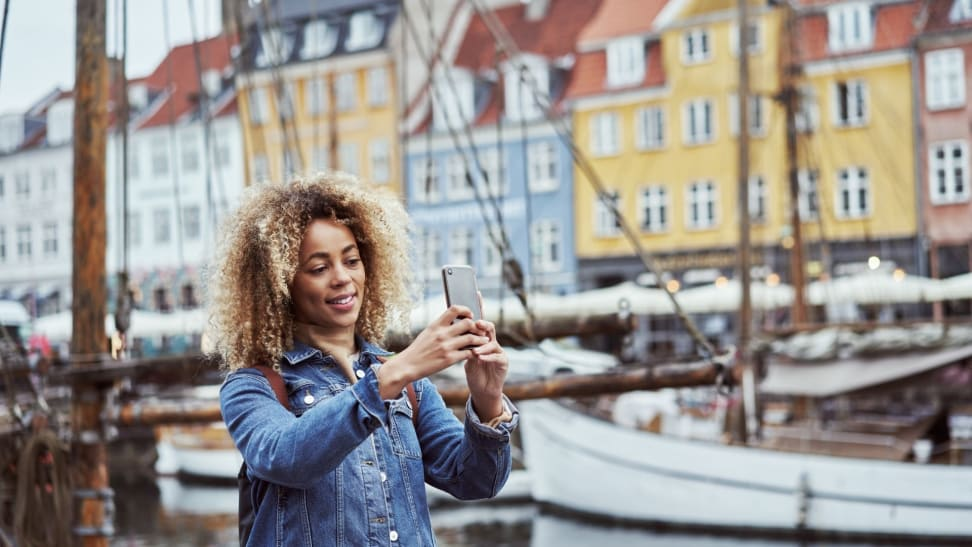 A woman in a denim jacket takes a photo of a canal with her smartphone