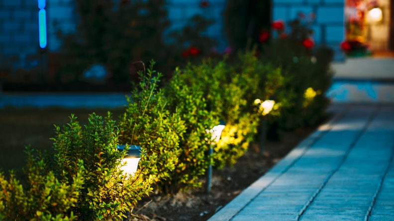 Solar-powered lights being using to illuminate pathway leading up to house at night.