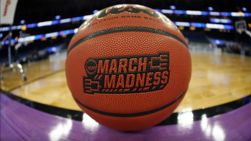 March Madness imprinted on a basketball on a basketball court