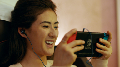 Image of a woman playing a Nintendo Switch with headphones in her ears
