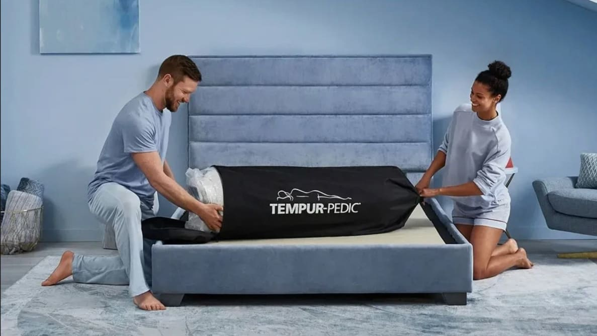 a couple open the Tempur-Pedic Cloud on their bed frame