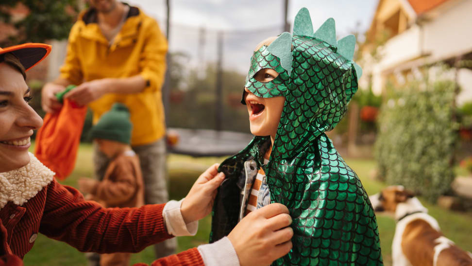 A young  boy dressed in a green dinosaur costume laughing
