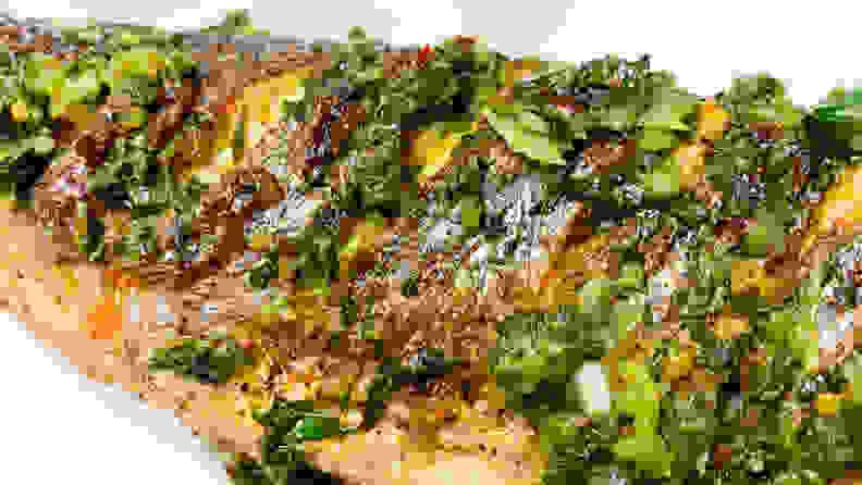 A photo of a whole branzino fish covered in vibrant green shisho chimichurri.