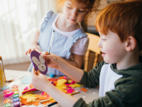 Two kids making Easter crafts at home