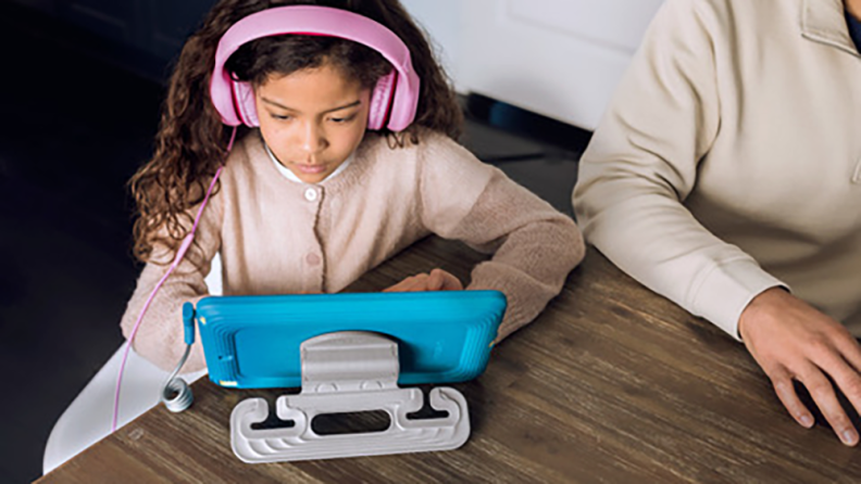 A young girl wearing headphones and looking at a tablet.