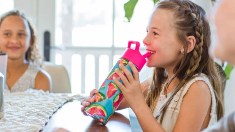 A girl smiles as she sips from a water bottle.