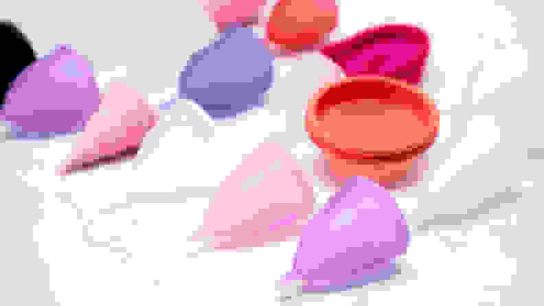 menstrual cups on white marble background