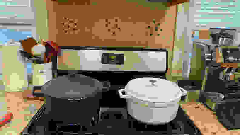 On a gas stovetop, on the left there's a black Perfect Pot with its lid on; to its right, there's a white Staub Dutch oven with its lid on. The Perfect Pot is taller than the white Dutch oven.