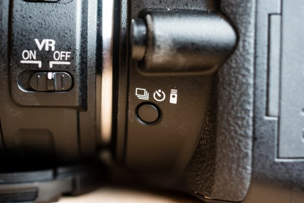 The drive mode button is placed in a rather inconvenient location under the lens mount.