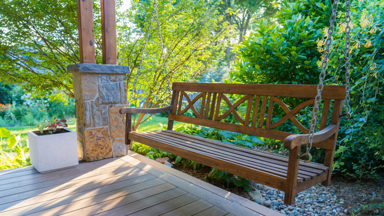 Wooden porch swing outdoors on a sunny day.