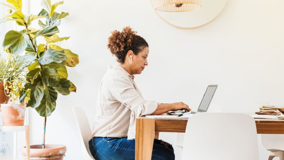 Woman sitting at dining table working on laptop