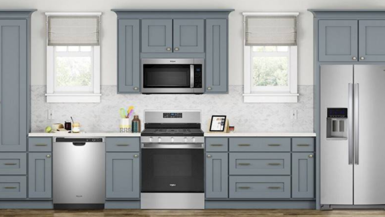 In the center of a modern kitchen featuring grey cabinets and white background, a Whirlpool WFG525S0JS gas range is fitted right below a microwave.