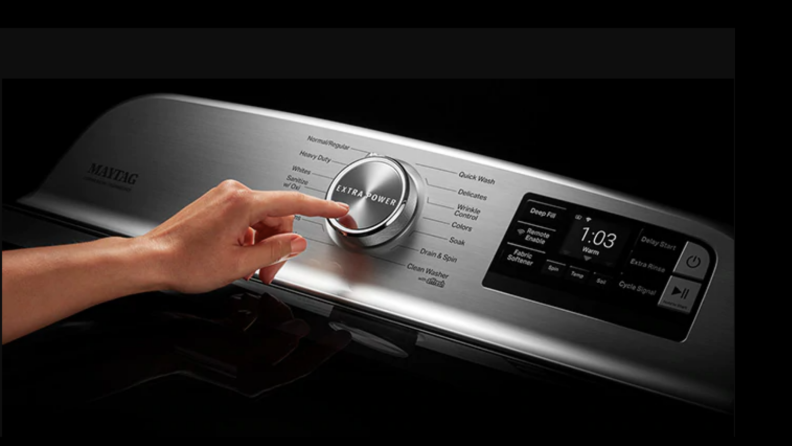 hand about to press button on washer