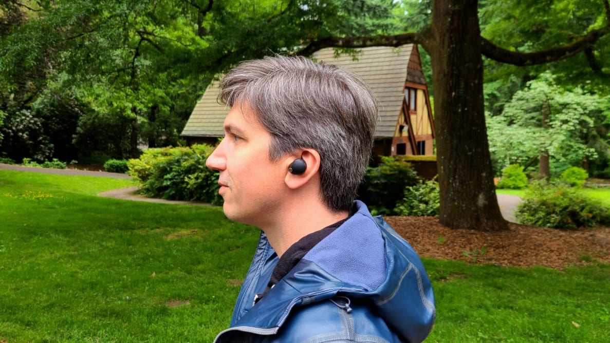 A handsome man wearing a pair of true wireless earbuds amongst the majesty of nature