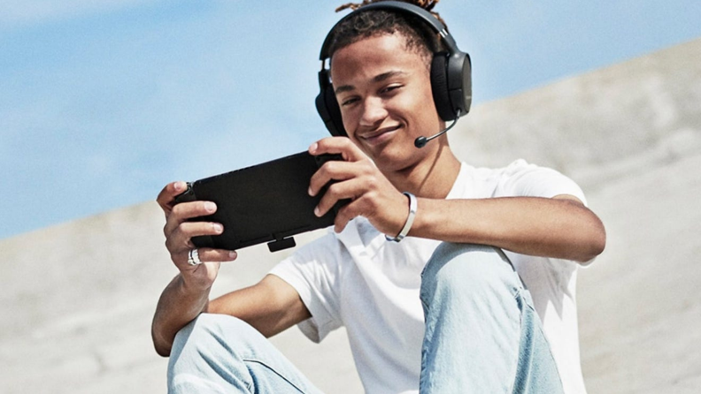 A person plays a video game outside wearing a headset.