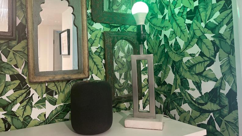 An Apple HomePod sits next to a smart light bulb
