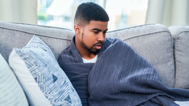 A person lounges on the couch wrapped in a blanket.