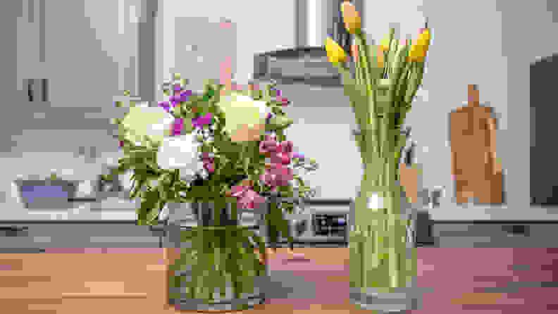 A purple arrangement next to a tulip arrangement