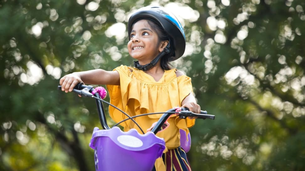 A girl beams while taking her bike for a ride outside. She's wearing a sunny yellow shirt and has a cute purple basket.