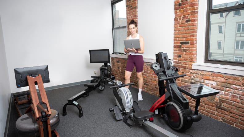woman standing in a room with many different rowing machines and a laptop.