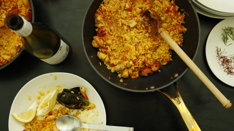 A pot full of cooked food in a black Frök pan is in the center of a black tabletop. Around the pan, some plates and a wine bottle are scattered around.