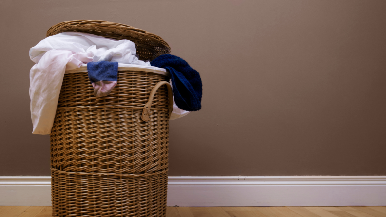 Clothes spill out of a wicker laundry hamper